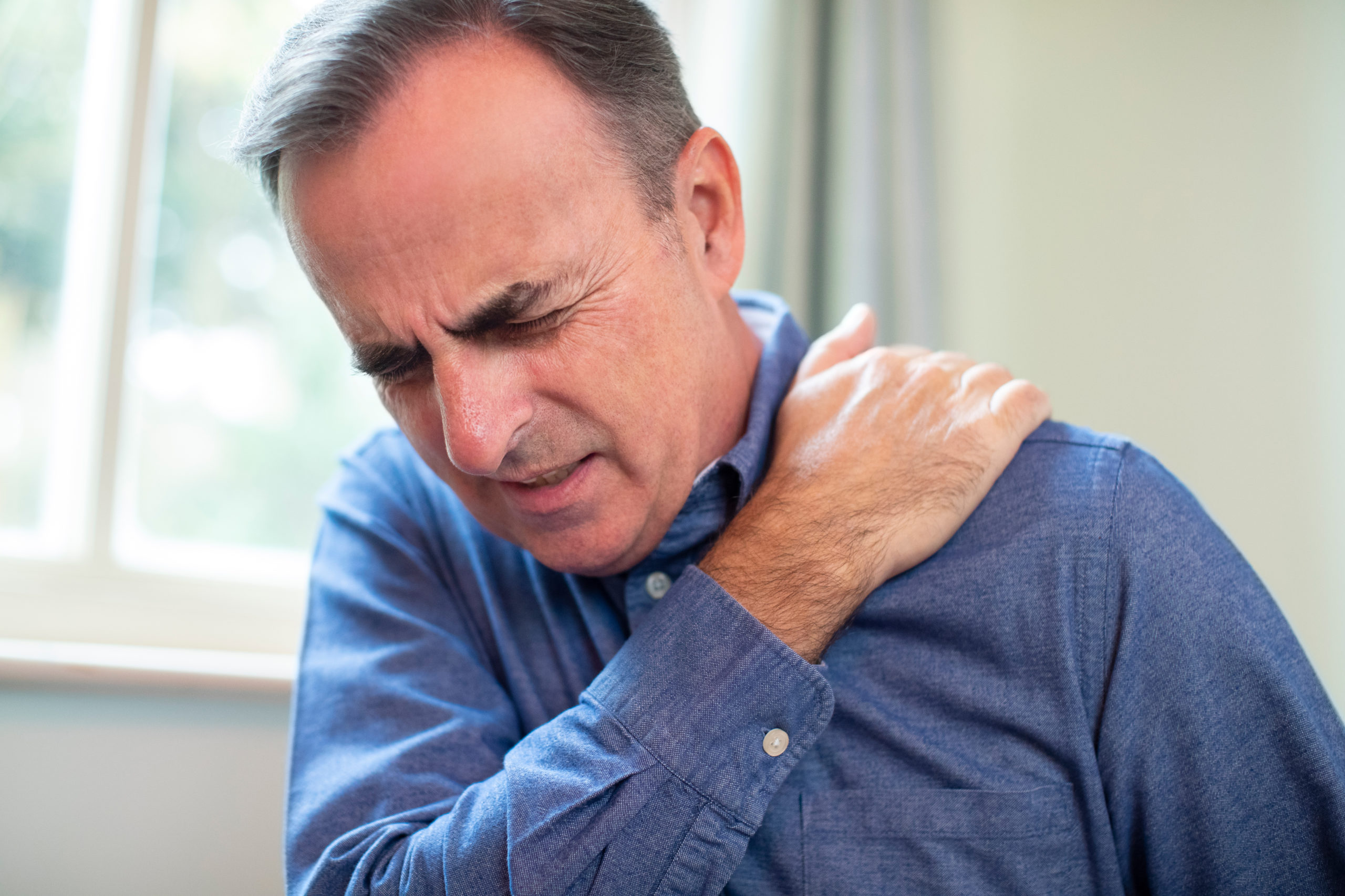 a man in pain holding his shoulder